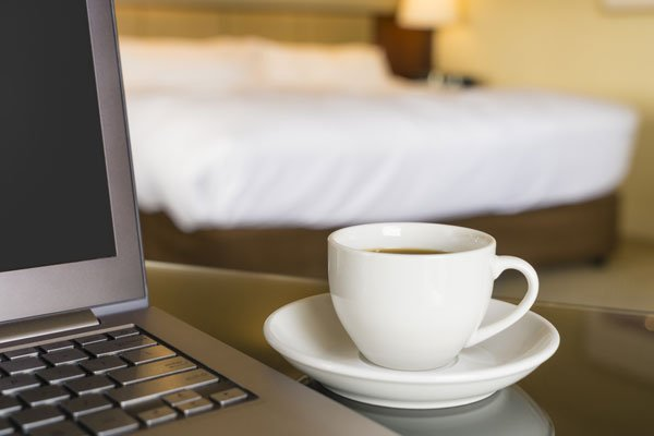 Laptop and coffee cup on desk in hotel room