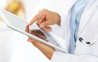Doctor speaking to hospital patient on ipad