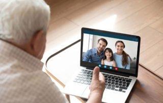 Senior man talking to family virtually on laptop